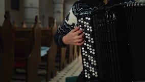 En kvinnlig musiker spelar dragspelet i gammal kyrka Tätt upp inomhus stock video