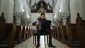 En kvinnlig musiker spelar dragspelet i gammal kyrka T?tt upp inomhus stock video