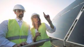 En kvinnlig och manliga sol- inspektörer har en diskussion nära en sol- enhet Grönt energibegrepp stock video