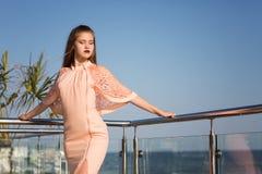 En kvinnlig på en naturlig blå havsbakgrund En attraktiv flicka som bär en rosa klänning En elegant dam En dam på en solig terras Arkivfoto