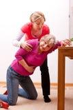 En kvinnlig pensionär kollapsar inomhus Arkivbild