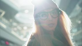 En kvinnlig stående för ung hipster i den stora gallerian sun arkivfoto