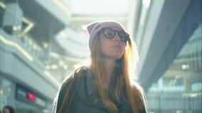 En kvinnlig stående för ung hipster nära shoppar fönster på solnedgången arkivbild