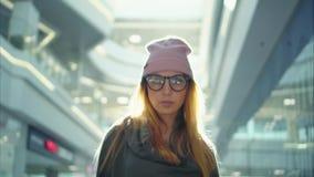En kvinnlig stående för ung hipster nära shoppar fönster på solnedgången arkivfoton