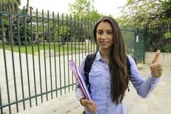 En kvinnlig student rymmer en limbindning med ett leende på ingången till högskolan Arkivfoton