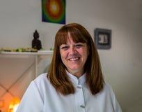 En kvinnlig terapeut ler på konsultationen av en terapicente Royaltyfri Foto