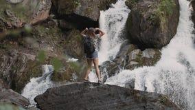 En kvinnlig turist klättrar vaggar upp och lyfter hans händer framme av en stor vattenfall Den lyckliga flickan tycker om framgån arkivfilmer