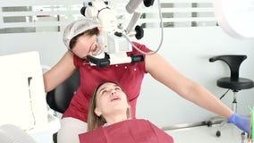 En kvinnlig yrkesm?ssig tandl?kare unders?ker en kvinnlig patient med ett stamotologic mikroskop i hennes kontor Stamotologist arkivfilmer