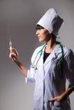 En kvinnligdoktor med en injektionsspruta arkivbild