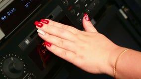 En kvinnligvänstersidahand sätter in en diskett in i den mini- diskettspelaren arkivfilmer