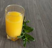 En kvist av mintkaramellen bredvid ett exponeringsglas av gul fruktsaft p? en tr?tabell arkivbilder