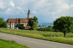 En kyrka med en sikt av sjön Constance arkivfoto