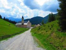 En kyrka ner en lång väg på en kulle i Fulpmes, Österrike royaltyfria bilder