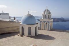 En kyrklig sikt på solnedgången i den Santorini ön Grekland arkivfoto