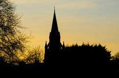En kyrklig tornspira i kontur mot en guld- solnedgång Arkivbild