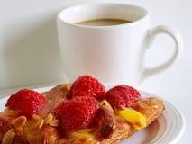 En läcker jordgubbewienerbröd och en vit kopp kaffe på vit bakgrund Royaltyfria Foton
