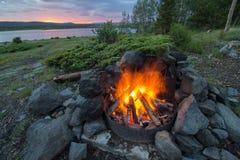 En lägereld bränner varmt på lakeshore en campingplats, som soluppsättningarna i bergen Arkivbild