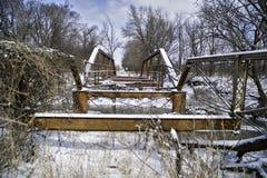 En länge övergiven bro rostar under vintersnön och den dystra himlen Royaltyfri Bild