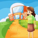 En lärare framme av skolabyggnaden Arkivfoto