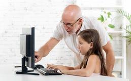 En lärare hjälper en skolflicka royaltyfria foton