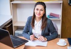 En lärare som sitter på skrivbordet royaltyfri fotografi