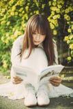 En läsning för ung kvinna på universitetsområdet Royaltyfria Foton