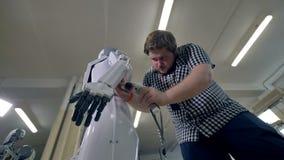 En låg sikt på en man som fäster den plast- kroppen för robotar stock video