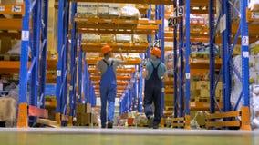 En låg sikt på två lagerinspektörer som bort går lager videofilmer