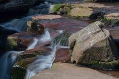 En lång exponering av den lilla vattenfallkaskaden över gräsplan och brunt vaggar arkivbild