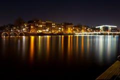 En lång exponering av en av de viktiga kanalerna i Amsterdam på natten royaltyfria bilder