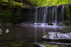 En lång exponering av en liten vattenfall i en avskild dalgång med frodiga täckte gräsplaner och mossa vaggar royaltyfria bilder