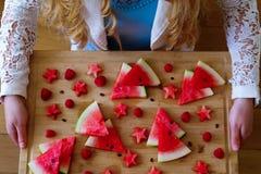 En lång hårflicka som rymmer ett vattenmelonmagasin royaltyfria bilder