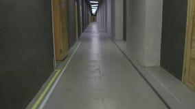 En lång korridor i kontoret Folket promenerar korridoren arkivfilmer