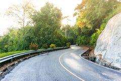 En lång krökt väg tillsammans med berget och skog i det guld- Arkivfoton