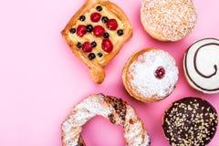En lång räcka av bakelse bakar ihop, donuts, kringlor, rosa färger, sötsaker, bästa sikt fotografering för bildbyråer