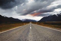 En lång rak väg in mot Mt-kocknationalpark under solnedgång royaltyfri fotografi