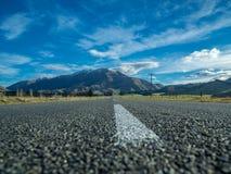 En lång rak väg som leder in mot ett korkat berg för snö i Nya Zeeland Arkivfoto