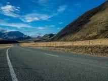 En lång rak väg som leder in mot ett korkat berg för snö i Nya Zeeland Royaltyfria Bilder