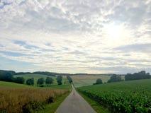 En lång väg i ett landskap av tysk bygd i Baden-Wurrtemberg, med vagnen Royaltyfri Fotografi
