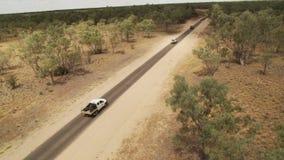 En lång väg med bilar och träd stock video