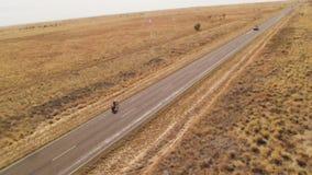 En lång väg med en cyklist som cyklar skottet stock video