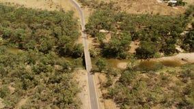 En lång väg med träd och en flod stock video