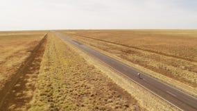 En lång väg och en person som cyklar på vägen arkivfilmer