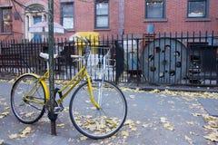 En låst gul cykel på gatan Arkivbilder