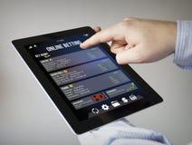En línea apostando a una tableta Foto de archivo libre de regalías