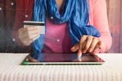 En línea que hace compras, hermosa mujer con la tarjeta de crédito a disposición que paga o que reserva en Internet fotos de archivo
