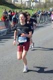 En löpare konkurrerar i Edinburghen vaggar - och - rullar den halva maratonen 2012 Arkivbild