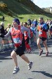 En löpare konkurrerar i Edinburghen vaggar - och - rullar den halva maratonen 2012 Royaltyfria Foton