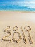 En la arena en el borde del océano se escribe 2011 Imagen de archivo libre de regalías