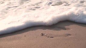 En la arena mojada, las impresiones del pie, quitan la onda, este lugar son convenientes para los pies almacen de metraje de vídeo
